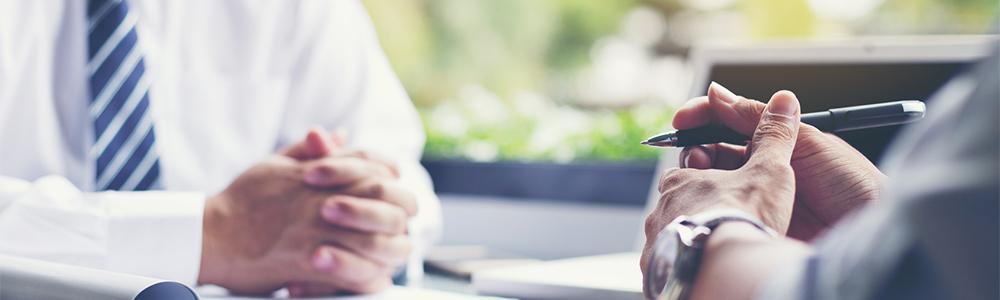 Chef und Mitarbeiter sitzen sich beim Vorstellungsgepräch gegenüber. Jetzt kommt es auf die richtige Gesprächsstrategie an, damit die Bewerbung erfolgreich wird.