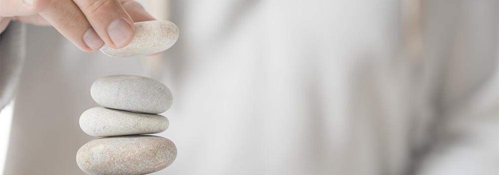 Vorsichtig setzt eine Person einen Stein auf einen bereits hohen Steinstapel. Auch in der Mitarbeiterführung muss man als Führungskraft mit Umsicht vorgehen, um Mitarbeiter aufzubauen.