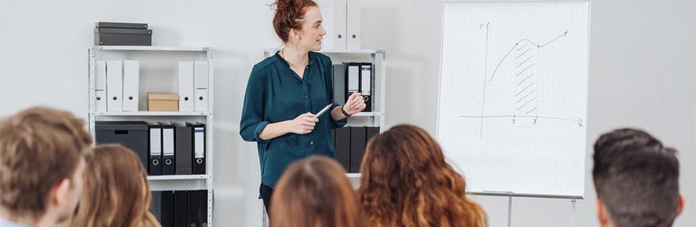 Eine Frau hält eine Präsentation vor Publikum. Sie ist sicher und leidet nicht unter Redeangst oder Lampenfieber beim Auftritt vor vielen Menschen.