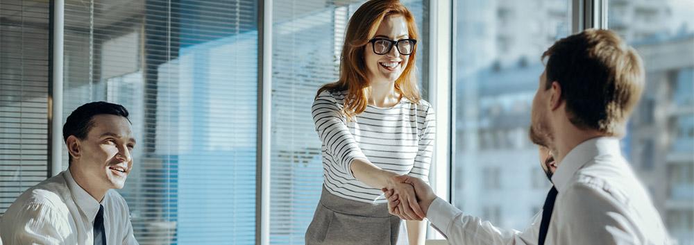 Eine Führungskraft begrüßt einen Mitarbeiter bei einem Meeting. Die richtige Gesprächsführung entscheidet über Erfolg oder Mißerfolg des Mitarbeitsgesprächs.