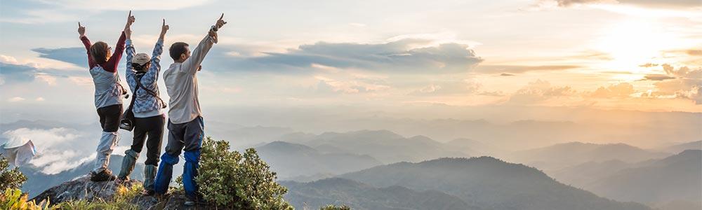 Drei Personen stehen auf dem Gipfel eines Berges und lassen Ihren Emotionen freien Lauf. Sie haben Ihr Ziel erreicht. Um den Gipfel im Verkauf zu erreichen bedarf es eines professionellen Verkaufstrainings, um richtig und erfolgreich zu verkaufen.